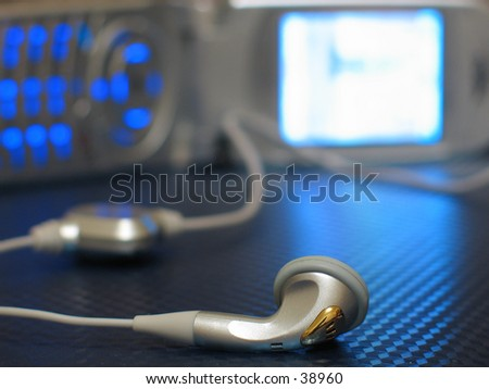 a macro of an earpiece and a cell phone in the background - stock photo
