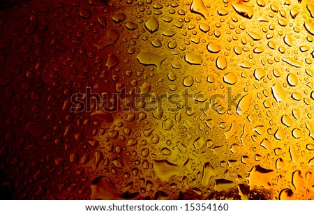 A macro of some water condensation on a glass full of amber colored beer. - stock photo