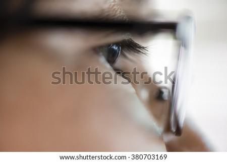 A macro photograph of eyes behind glasses - stock photo