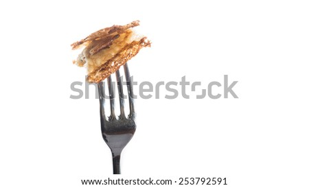 A macro shot of a bite-sized piece of pancake on a fork, shot against a white background. - stock photo