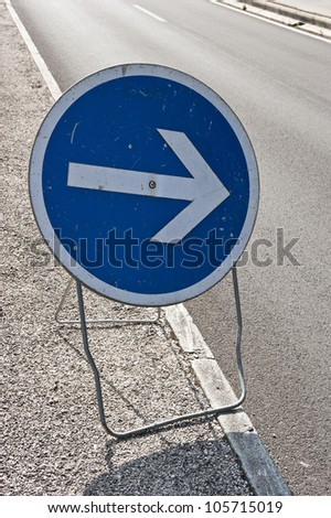 "A macro shot of a blue, circular ""Left Turn"" road sign in Villefranche-sur-Mer, France."