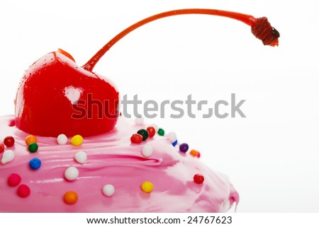 A macro shot of a cherry on top of a cupcake - stock photo