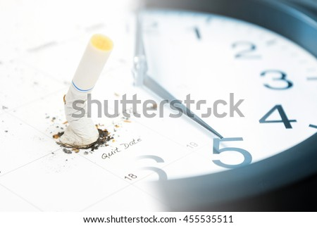 A macro shot of a clock and cigarette.