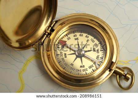 A macro shot of a navigating compass on top of a recreational map. - stock photo