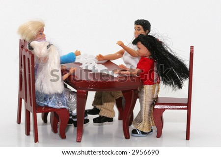 A macro shot of a toy family sitting at a dining table. isolated on white