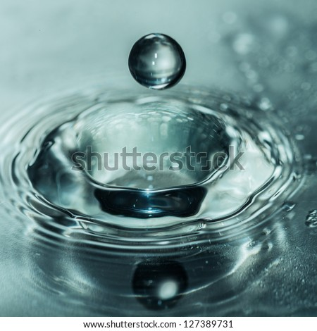 A macro shot of a water drop about to fall into a hole created by another water drop. - stock photo
