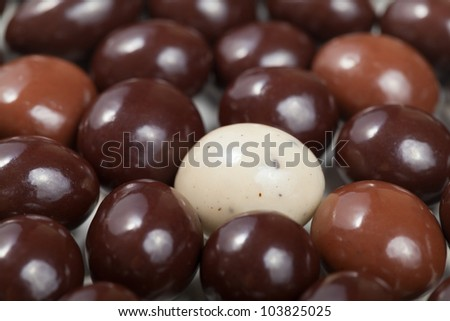 A macro shot of a white chocolate covered espresso bean surrounded by dark chocolate espresso beans. Shallow Depth of Field. - stock photo