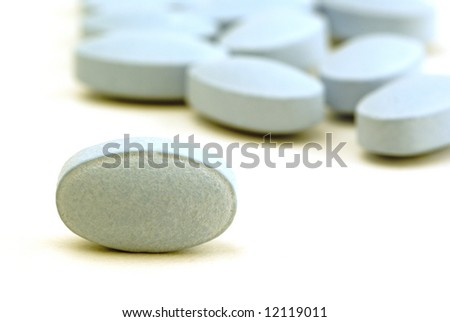 A macro shot of blue pills on a white background - stock photo
