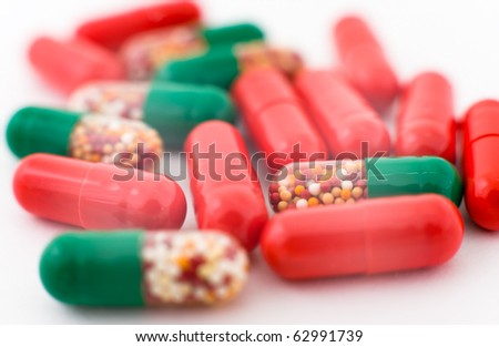 a macro shot of medicines, red and green capsules - stock photo