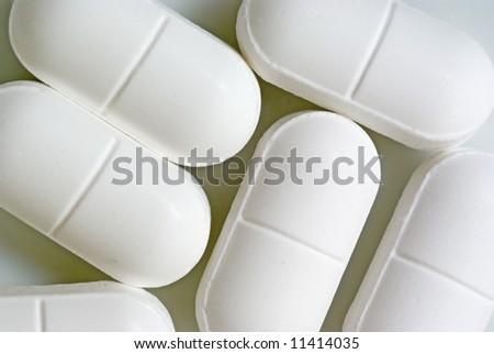 A macro shot of some pills on white - stock photo