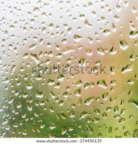 A macro shot of some raindrops on a pane of glass. - stock photo