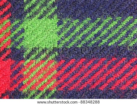 A macro view of a piece of blue cloth with green and red stripes