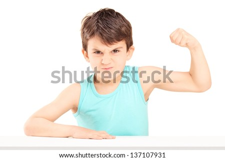 A mad child showing his muscles seated on a table isolated on white background - stock photo