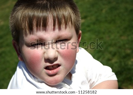 """A mad little boy grimacing """"up"""" at an adult - stock photo"""