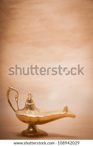 A magic genie lamp, isolated on a sand color background, in a studio shot. - stock photo