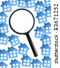 A magnifying glass and houses isolated against a white background - stock photo