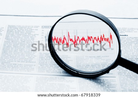 A magnifying glass focusing on a graph in the business section of the newspape - stock photo
