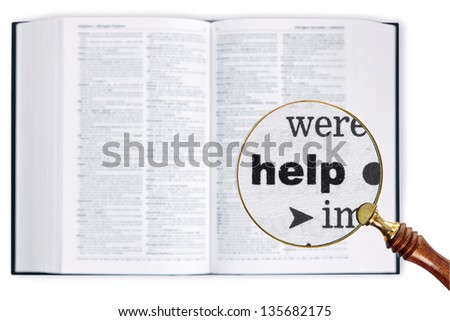 A magnifying glass held over a dictionary looking at the word Help enlarged - stock photo