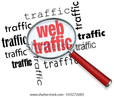 A magnifying glass hovering over several instances of the word traffic, symbolizing the search for ways to boost and analyze web traffic on the Internet - stock photo