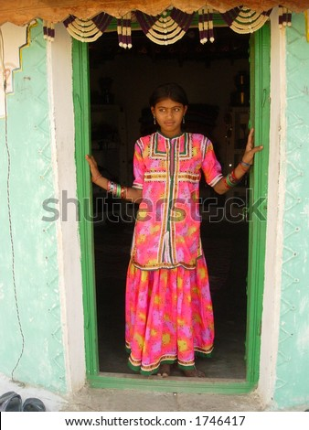 a maiden posing on the door of a home in a village in india - stock photo