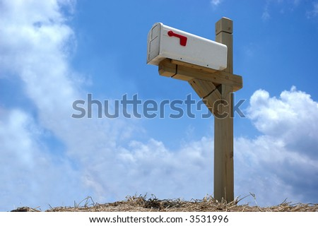 A mailbox mounted on wood stand in clear blue sky background - stock photo