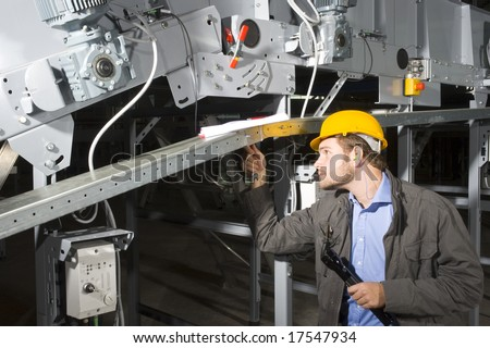 A maintenance engineer at work, tightening bolts of an industrial appliance