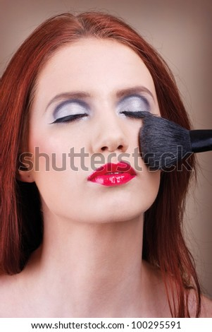 A make-up artist applying a powder on a beautiful woman's face
