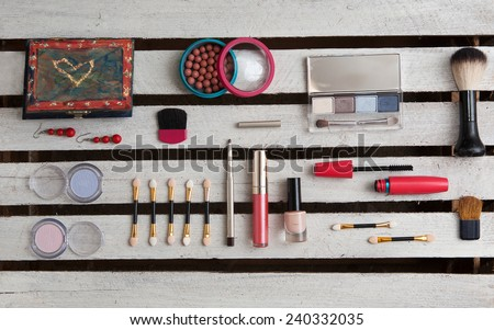 a makeup accessories on white wooden background - stock photo