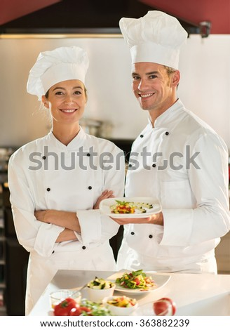 A male and a female cook chef are standing in a professional kitchen presenting a plateful with fine food. They are looking at camera, wearing white chef clothes and hat. Blurred background. - stock photo