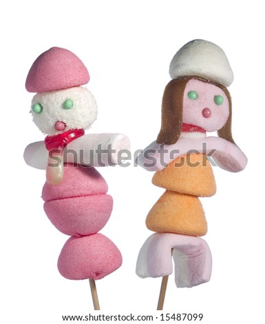 A male and a female figurine made out of candies on a stick over a white background.