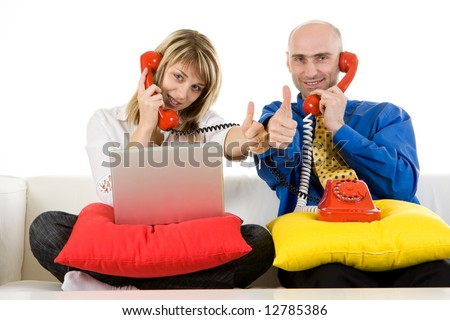 A male and female business executive sitting on sofa with a white laptop and red phone with a thumbs up expression.