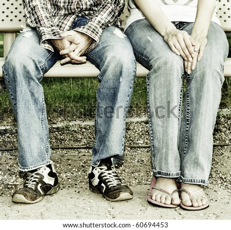 A male and female sitting on a bench./ Couple Sitting on a Bench - stock photo