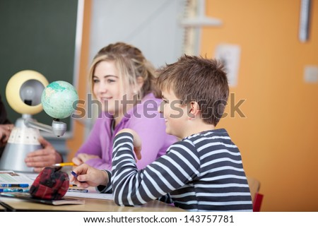 A male and female teenager smiling while learning geography in the classroom. - stock photo