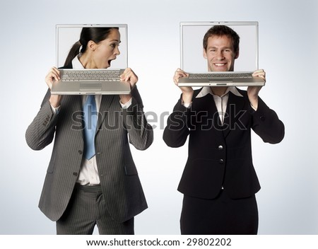 A male and female with swapped heads on their laptops - stock photo