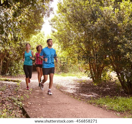 A male and two female friends running on a jogging trail surrounded by trees in the late morning shadows wearing t-shirts and black pants