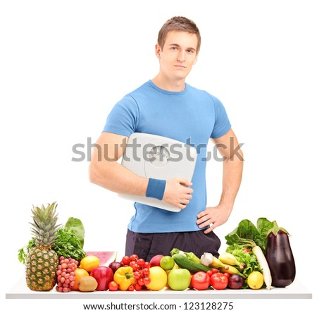 A male athlete holding a weight scale behind a table full of fruits and vegetables isolated on white background