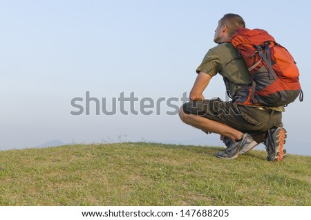 A male backpacker rests on hilltop looking at the sky. - stock photo