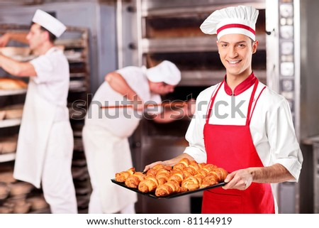 A male baker holding freshly baked croissants in bakery - stock photo