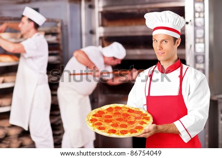 A male baker holding freshly baked pizza in bakery - stock photo