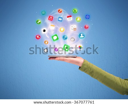 A male caucasian hand holding a mobile phone tablet from profile view with digital application logos above the device illustration concept - stock photo