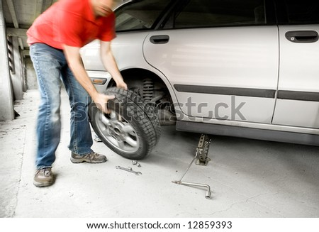 A male changing a tire on a car in a garage - stock photo