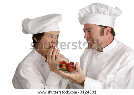 A male chef feeding a fresh strawberry to a female chef.  Isolated on white. - stock photo