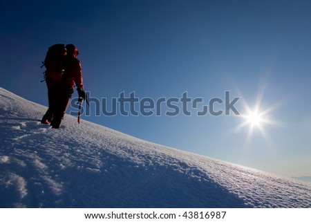 A male climber , dressed in red, climbs down a snowy slope. Winter clear sky day. - stock photo