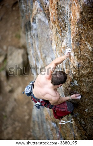 A male climber, viewed from above, climbs a very high and steep crag. Shallow depth of field is used to isolate the climber with focus on the hands and head - stock photo