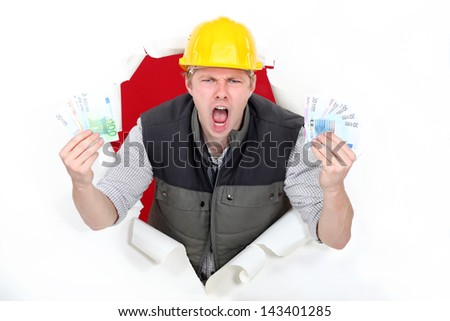 A male construction worker with plenty of cash. - stock photo