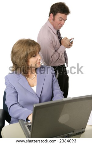 A male coworker spying over a female coworker's shoulder and taking notes on what he sees.  Isolated on white.  Focus on female.