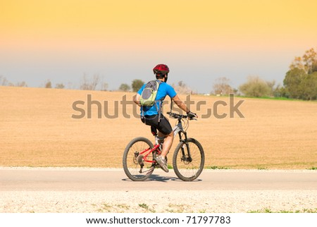 A male cyclist riding a bike over field