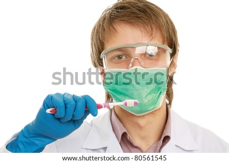 A male dentist with tools in his hands, isolated on white, side-view - stock photo