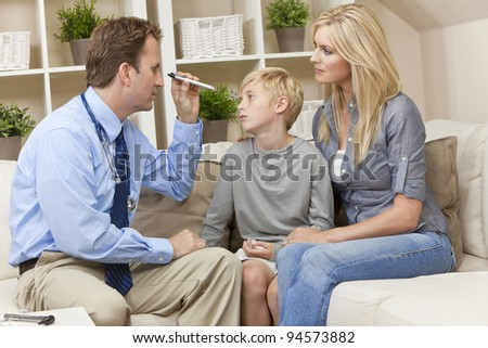 A male doctor examining a sick boy child with his mother during a home visit - stock photo