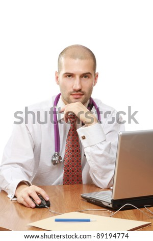 A male doctor smiling at the table in front of a laptop